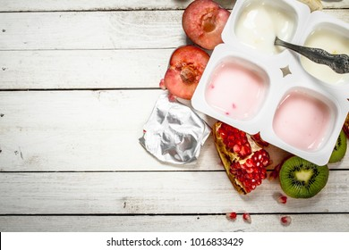 Various fruit yoghurts. On a white wooden table.