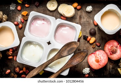 Various fruit yoghurts. On a wooden background.
