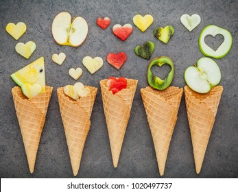 Various fruits in waffle cones  and heart shape of fruits setup on dark stone background . Valentine 's day and Sweet menu concept.