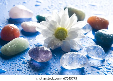various gems stones with a white daisy over blue background with drops of water