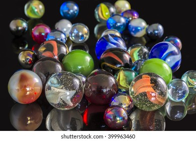 Various glass marbles on a reflective black surface