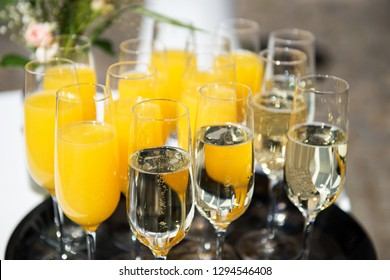 Various glasses of champagne and orange juice on a tray with a pink rose in background
