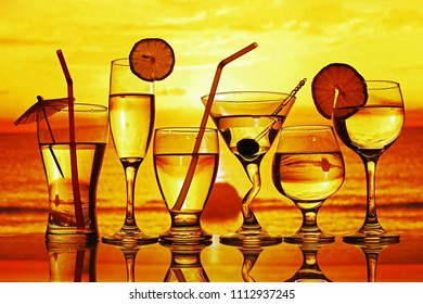Various glasses with drinks in sunset overlooking the sea