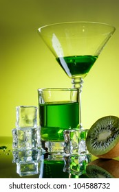 Various glasses with green liquid and ice cubes