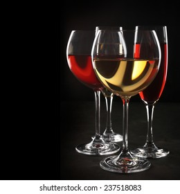Various glasses of red and white wine with abstract pattern on black background.