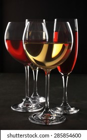Various glasses of red and white wine with abstract pattern on black wooden background.