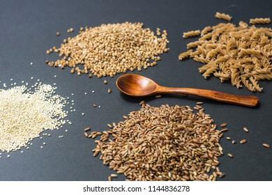 Various gluten-free products: buckwheat, quinoa, einkorn (polba, spelt, eincorn, emmer wheat) pasta and soba (buckwheat flour noodles). On a black background. Top view
