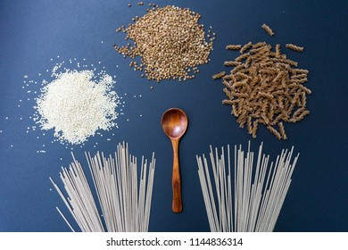 Various gluten-free products: buckwheat, quinoa, einkorn (polba, spelt, eincorn, emmer wheat) pasta and soba (buckwheat flour noodles). On a black background. Top view