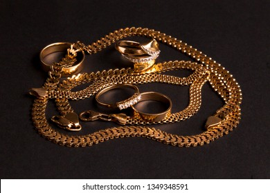 Various gold jewelry, chaotically arranged: wedding rings, engagement ring, chain, bracelet. Isolated on a matte black background.