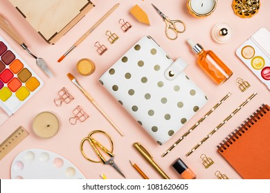 Various golden, orange and white stationary and office tools and accessories knolled together on pastel background: planner, brushes, pencils, clips, rulers, scissors, etc. Flatlay