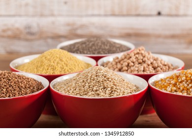 Various grains and cerelas in red bowls consisting of buckwheat, rice, corn, millet, chickpea and chia on wooden background - copy space