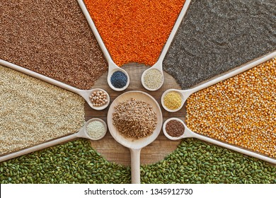 Various grains, seeds and cerelas on the table in a colorful arrangement - healthy whole food