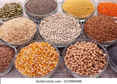 Various grains and seeds in glass bowls, diversified nutrition concept - closeup
