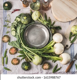 Various green seasonal vegetables around plate on kitchen table. Healthy  vegetarian cooking concept. Garden vegetables eating. Organic food