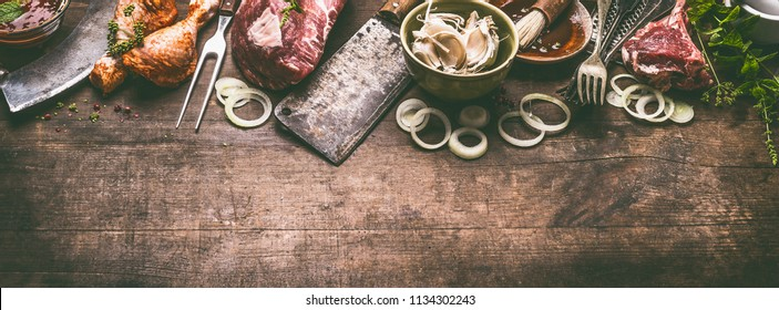 Various grill and bbq meat : chicken legs, steaks, lamb ribs with vintage kitchenware kitchen utensils:  Meat Fork and Butcher Cleaver and herbs knife. Sauces and ingredients for grilling, top view