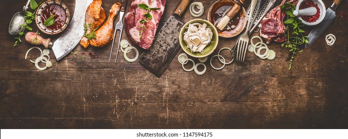 Various grill an bbq meats on rustic wooden background with aged kitchen and butcher tools, herbs, spices, seasoning and sauce, top view, border