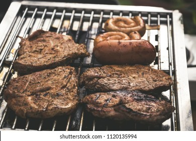 various grilled meat grilling on a gas barbecue with sausages, steaks on a grillage