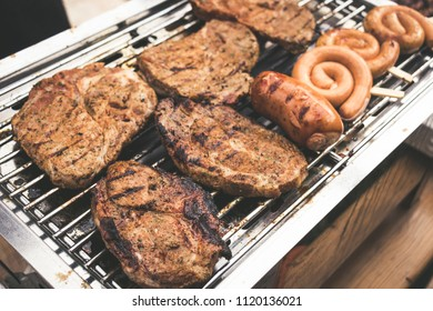 various grilled meat grilling on a gas barbecue with sausages, steaks