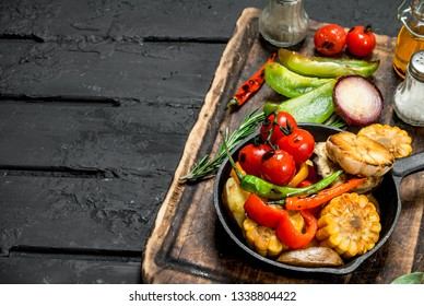 Various grilled vegetables in a pan with spices on a wooden Board. On a black rustic background.