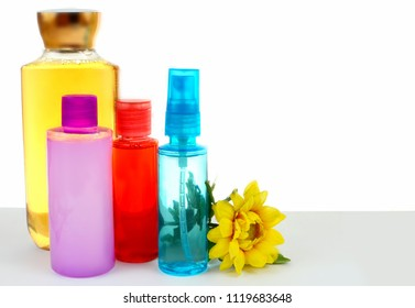 Various hair and body beauty products in bright colors with a cheerful yellow chrysanthemum on white background. Copy space.