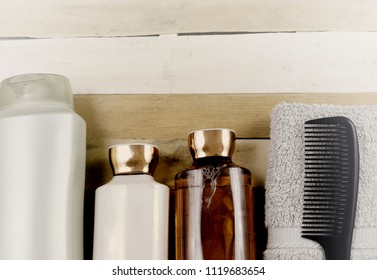 Various hair and body beauty products on a wooden background with vintage filter. Includes a black comb and green washcloth