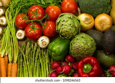 Various healthy fresh produce including carrot, mushroom, radish, onion, potato, avocado, broccoli, bell pepper, artichoke, and tomatoes on the wooden background. Flat lay image of various vegetables.