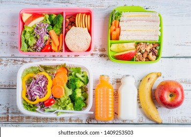 Various of Healthy lunch boxes of sandwich. Kid bento pack for school set in plastic package, salad box, banana and apple with orange juice, milk. Top view.