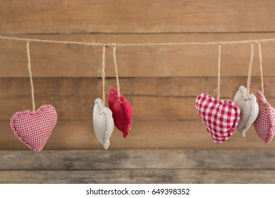 Various heart shape decoration hanging on string against wooden background