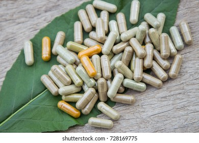 Various of herbal medicine in capsules on herb leaf for healthy eating lifestyle