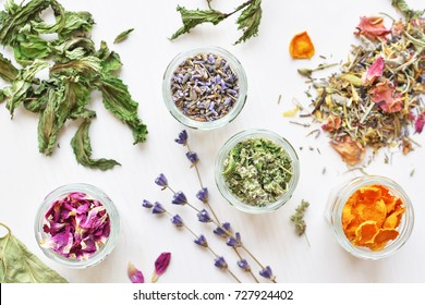 various herbal tea ingredients in glass jars over white wooden background