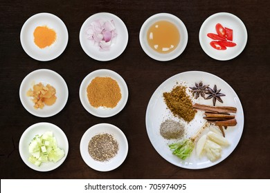 various herbs cinnamon, star anise, sarlic, black pepers, corriander root  in white plate on black brown wooden background