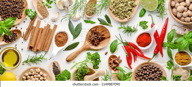 Various herbs and spices. Flat lay of spices ingredients chilli ,pepper, garlic,dries thyme, cinnamon,star anise, nutmeg,rosemary, sweet basil and kaffir lime on wooden background.