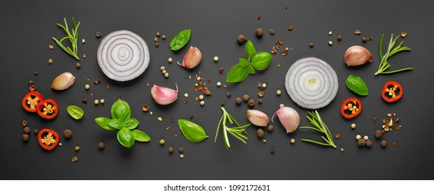 various herbs and spices on black background, top view