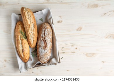Various homemade bread with rosemary in rustic wooden box, top view. Sourdough mini baguette wheat and rye bread.