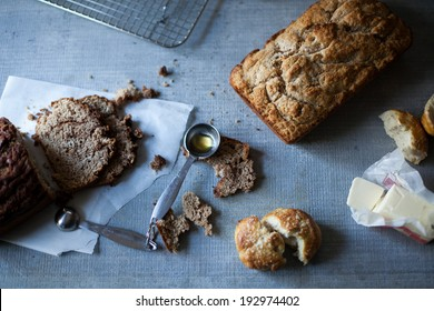 Various homemade breads on blue textured table with honey and butter