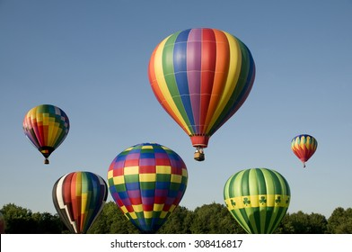 Various hot-air balloons with colorful envelopes ascending or launching at a ballooning festival