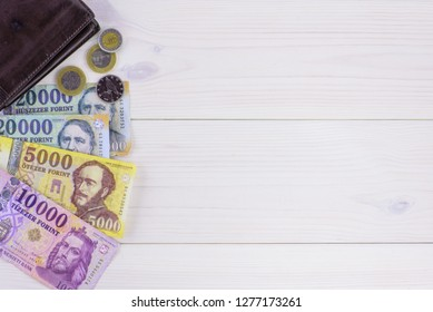 Various Hungarian banknotes and coins on a wooden table, 5-10-20 thousand forints and a wallet. Europe Hungary.