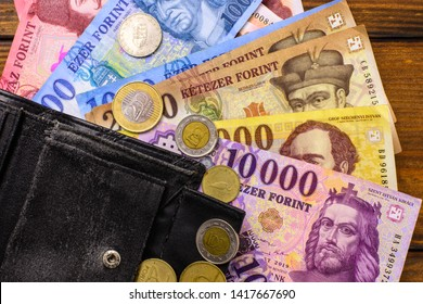 Various Hungarian banknotes and coins on a wooden table, 1-2-5-10 thousand forints and a wallet. Europe Hungary.