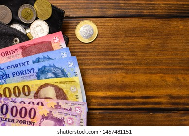 Various Hungarian banknotes and coins on a wooden table, 1-2-5 thousand forints and a wallet. Europe Hungary.