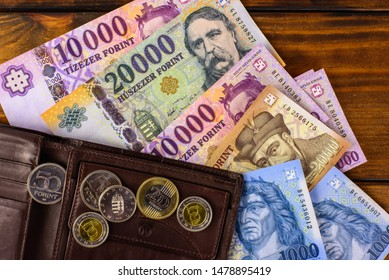 Various Hungarian banknotes and coins on a wooden table, 1-2-10-20 thousand forints and a wallet. Europe Hungary.