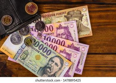 Various Hungarian banknotes and coins on a wooden table, 2-10-20 thousand forints and a wallet. Europe Hungary.