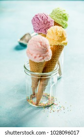 Various of ice cream flavor in cones pink (strawberry), purple (blueberry), green (pistachio, green tea, lime) and yellow (mango, banana) setup on blue wooden background . Summer and Sweet menu