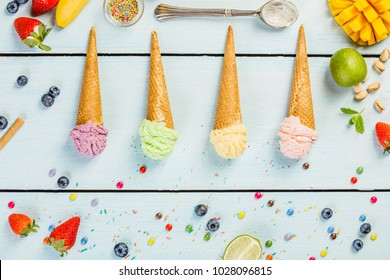 Various of ice cream flavor in cones pink(strawberry), purple (blueberry), green (pistachio, green tea, lime) and yellow (mango, banana) setup on blue wooden background . Summer and Sweet menu concept