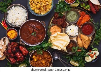 Various Indian dishes featuring  rogan josh, chicken tikka masala, biryani, tandoori chicken, kebabs and mixed indian platter with samosa, pakoras, onion bajis, poppadoms , naan and dips, top view