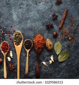 Various indian spices in wooden spoons, herbs and nuts on dark stone table. Colorful italian spices, top view. Organic food, healthy lifestyle, space for text