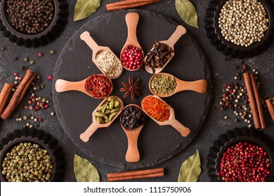 Various indian spices in wooden spoons, seeds, herbs on dark stone table. Colorful spices, top view. Organic food, healthy lifestyle, space for text