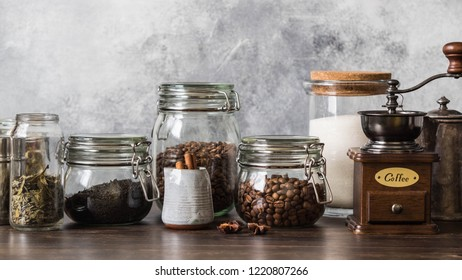 Various ingredients for making hot drinks - coffee, herbal tea, black tea. Glass jars with coffee beans, tea, sugar, coffee grinder and milkman with cinnamon on dark wood table