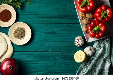 Various ingredients for Middle Eastern cuisine dish - muhammara - red bell pepper paste with walnuts on a dark green wooden background