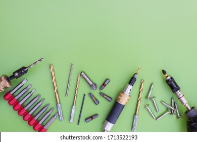 Various interchangeable screwdriver bits, countersink, drill bits, magnetic  bit holders and screws. Green background with copy space.