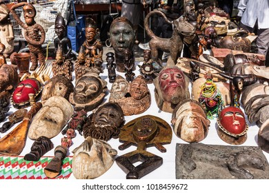 Various interesting wooden masks and figures of African culture on sale at the flea market in Paris. France